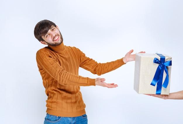 Uma caixa de presente branca com fita azul está sendo oferecida ao homem e ele a pega com as duas mãos.