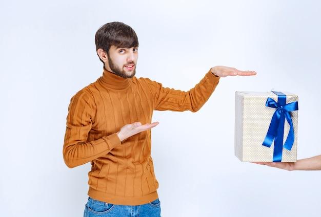 Uma caixa de presente branca com fita azul está sendo oferecida ao homem e ele está apontando para ela.