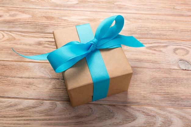 Uma caixa de presente com a tabela de madeira da fita azul. vista do topo