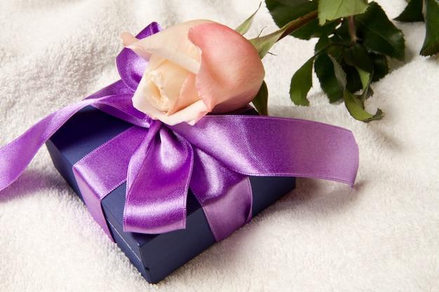 Uma caixa de presente com fita de lavanda e rosa
