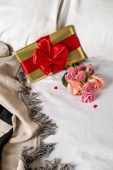 Uma caixa de presente e flores estão na cama de manhã cedo. conteúdo para lua de mel e namorados no dia dos namorados.