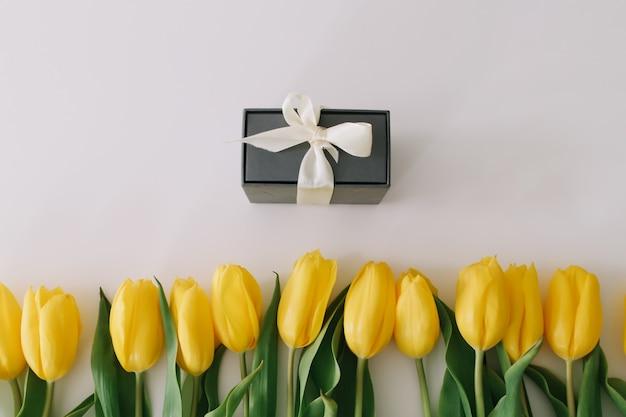Uma caixa de presente e tulipas amarelas frescas em branco.