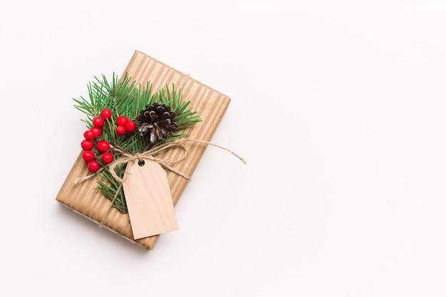 Uma caixa de presente em um invólucro de artesanato com um galho de uma árvore de natal e um formulário em branco de madeira para texto