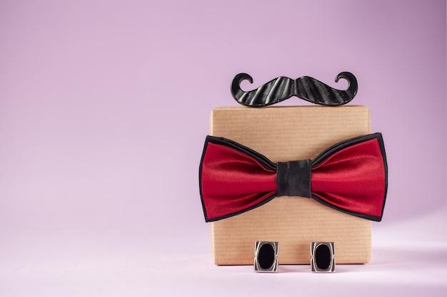 Uma caixa de presente embrulhada em papel artesanal e amarrada com a gravata borboleta. dia dos pais.