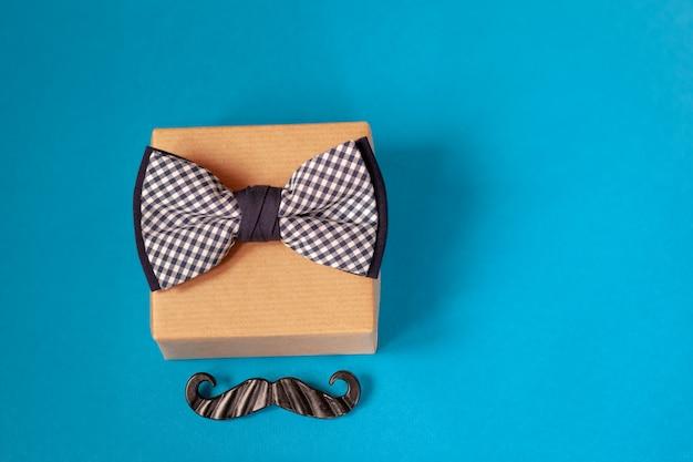 Uma caixa de presente embrulhada em papel ofício e amarrada com a gravata borboleta azul.