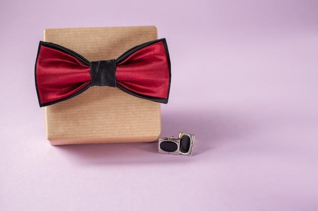 Uma caixa de presente embrulhada em papel ofício e amarrada com a gravata borboleta