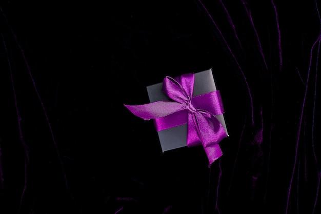 Uma caixa de presente preta de luxo com fita violeta