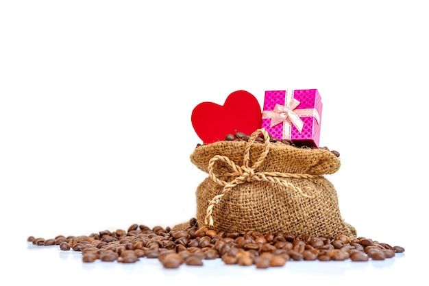 Uma caixa de presente rosa e um papel de coração vermelho no saco de serapilheira de café com grãos de café