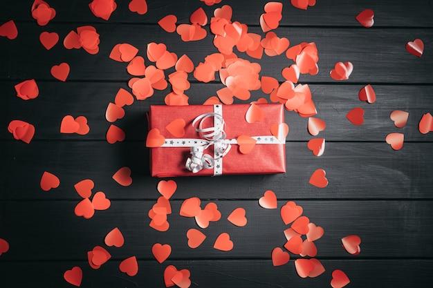 Uma caixa de presente vermelha encontra-se em uma mesa preta entre pequenos corações vermelhos. conceito de são valentim.