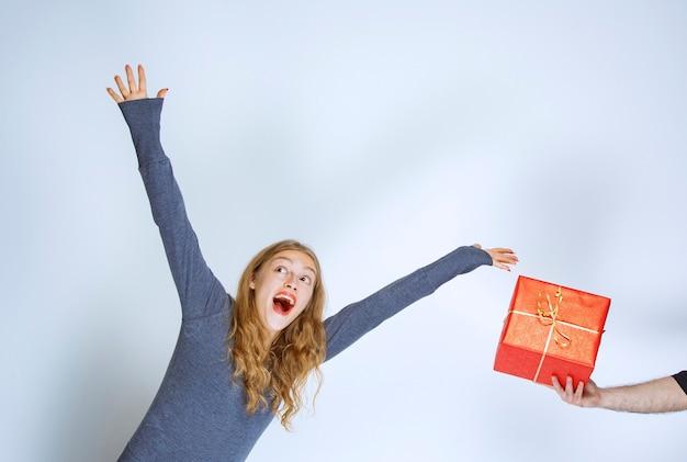 Uma caixa de presente vermelha está sendo oferecida a uma menina loira e ela está ansiosa para aceitá-la.