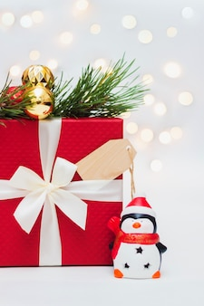 Uma caixa de presente vermelha uma forma de madeira para saudar o texto um galho de uma árvore de natal.