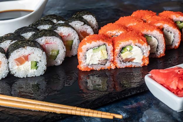 Uma caixa de sushi nigiri, uramaki califórnia, filadélfia, em um prato de pedra preto. menu de sushi em uma caixa de transporte branca sobre um fundo de madeira.