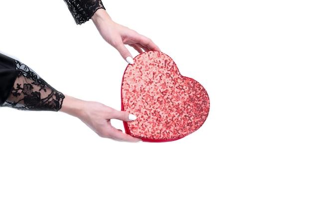 Uma caixa em forma de um coração vermelho coberto com lantejoulas vermelhas brilhantes em um estilo vintage em mãos femininas isoladas em um fundo branco.