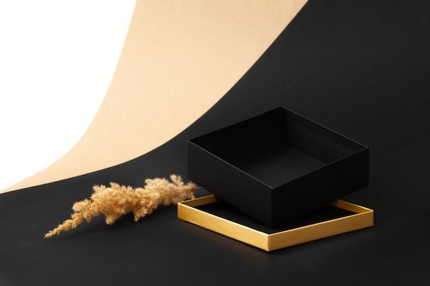 Uma caixa preta aberta sobre uma tampa dourada e uma decoração de juncos secos