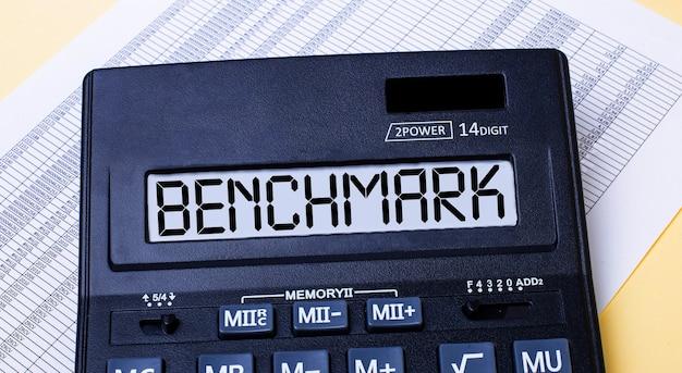 Uma calculadora chamada benchmark está na mesa perto do relatório. conceito financeiro