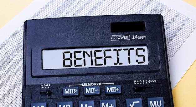 Uma calculadora chamada benefícios está na mesa perto do relatório. conceito financeiro