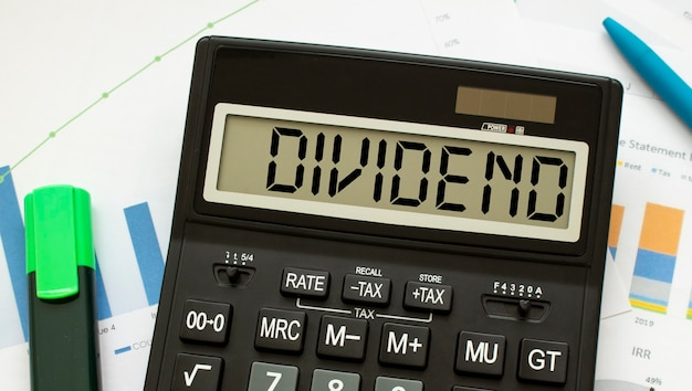 Uma calculadora chamada dividend encontra-se em documentos financeiros no escritório