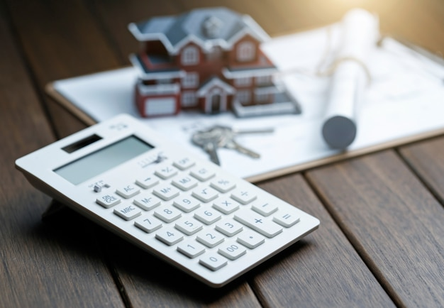 Uma calculadora na frente de um modelo de casa de villa com um plano