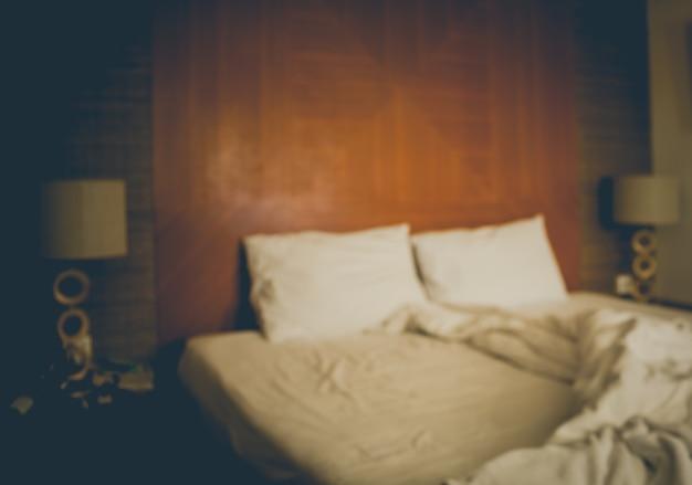 Uma cama bagunçada turva com lençóis brancos em tom vintage.