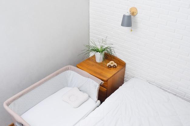 Uma cama lateral para um recém-nascido no fundo de uma parede de tijolos brancos.