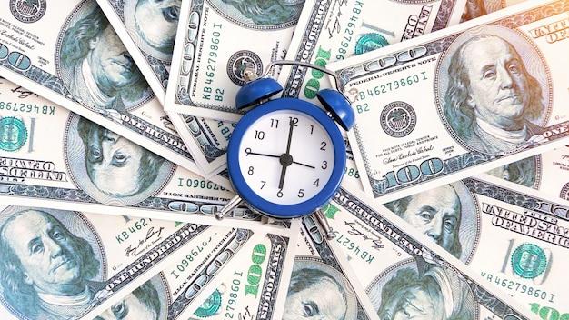 Uma camada de dinheiro com um relógio no centro. ideia de finanças