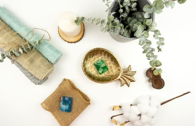 Uma camada plana de toalhas de algodão, sabonete feito à mão, um pote com eucalipto e um galho de algodão em uma mesa branca em um banheiro moderno