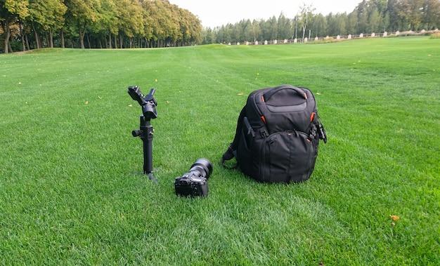 Uma câmera, bolsa e gimbal sentado na grama exuberante em um parque da cidade.