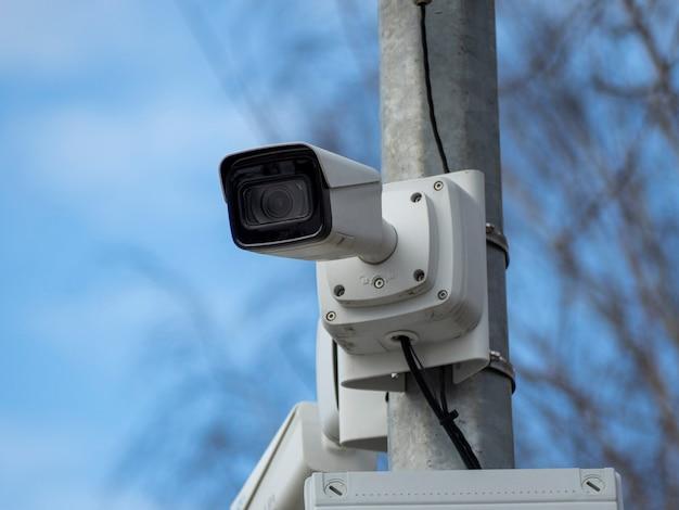 Uma câmera de segurança em um poste contra um céu azul. tecnologias de segurança