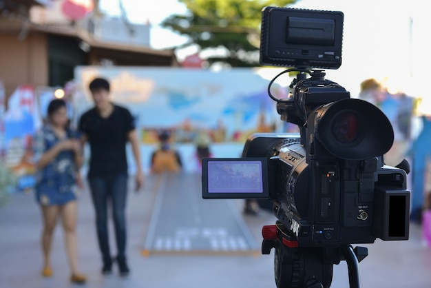 Uma câmera de vídeo que usa streaming de vídeo ao vivo com atores andando na frente