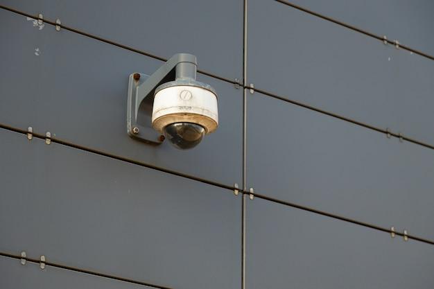Uma câmera de vigilância branco-cinza na parede de metal cinza