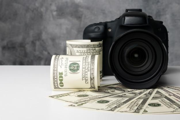 Uma câmera digital preta e notas de banco em uma mesa branca com fundo grunge.