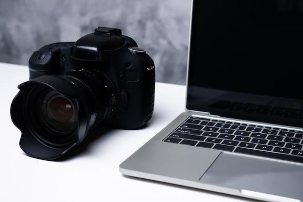 Uma câmera digital preta e um laptop em uma mesa