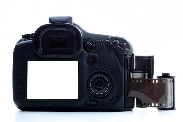 Uma câmera digital preta e um rolo de filme sobre um fundo branco.