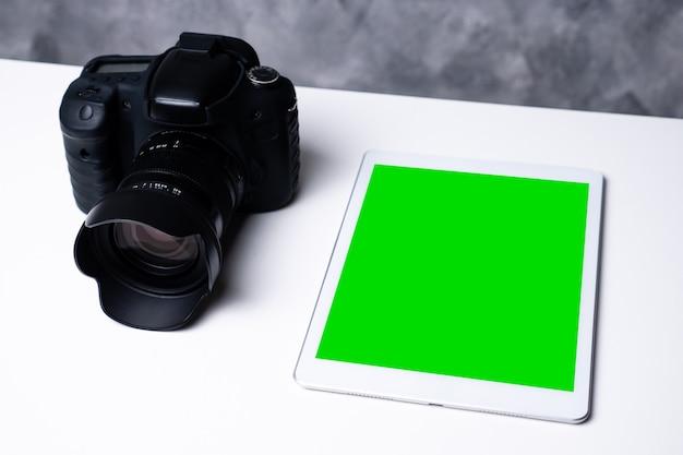 Uma câmera digital preta e um tablet de tela em branco em uma tabela.
