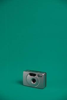 Uma câmera do rolo do estilo do vintage da cor cinzenta em um fundo verde da água.