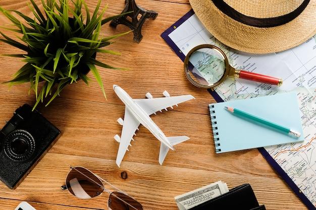 Uma câmera, óculos de sol, dinheiro em uma carteira, um chapéu de palha e um telefone celular.