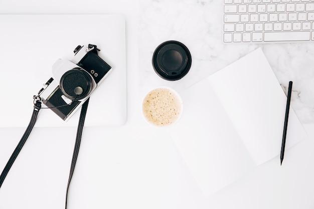 Uma câmera retro do vintage velho na tabuleta digital; xícara de café; papel; lápis e teclado na mesa branca