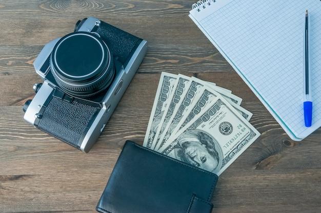 Uma câmera retro, uma bolsa com dinheiro e um caderno com uma caneta em uma mesa de madeira.
