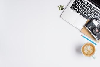 Uma câmera velha; caderno no laptop com lápis azul e xícara de cappuccino no fundo branco