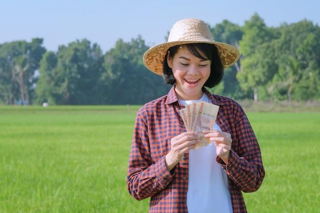 Uma camponesa com uma camisa listrada está de pé com um rosto sorridente no campo segurando as notas.