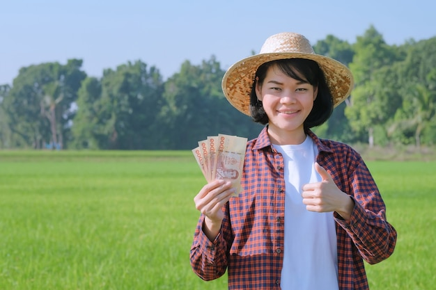 Uma camponesa com uma camisa listrada está posando de alegria e segurando notas em um campo.