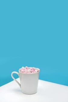 Uma caneca branca com marshmallows em uma mesa branca contra uma parede azul com espaço de cópia.