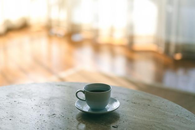 Uma caneca branca de café quente na mesa perto da cortina da casa