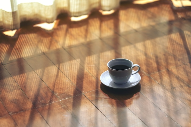 Uma caneca branca de café quente no chão de madeira perto da cortina da casa