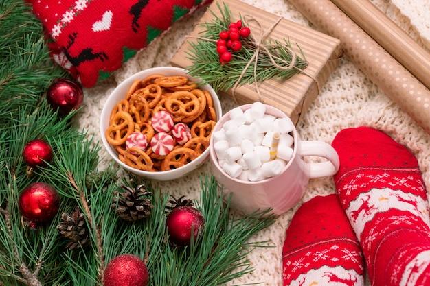 Uma caneca com caixa de presente de marshmallow envoltório de artesanato galho de uma árvore de natal uma tigela de pretzels