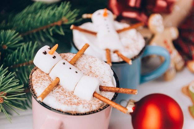 Uma caneca com chocolate quente em uma mesa de madeira com um homem de marshmallow que está descansando em uma caneca