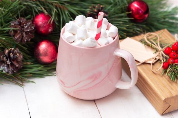 Uma caneca com marshmallow de bebida quente perto de um galho de árvore de abeto. decorações de ano novo de natal
