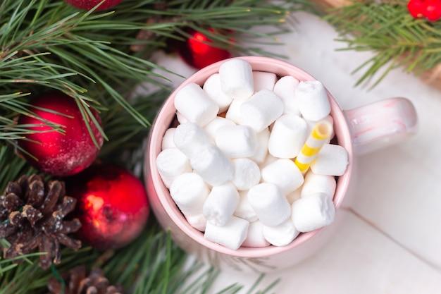 Uma caneca com marshmallow perto de um galho de um pinheiro com bolas de brinquedo e decorações de natal