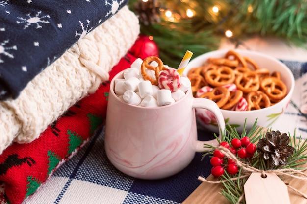 Uma caneca com marshmallow perto de uma pilha de suéteres de inverno uma tigela de pretzels enfeites de natal