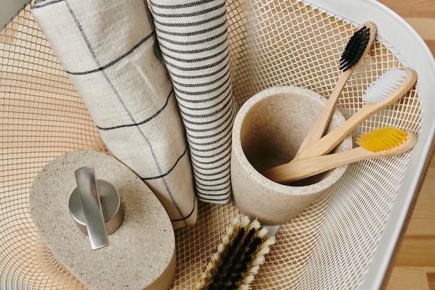 Uma caneca com três escovas de dente, sabonete líquido, escova e duas toalhas de algodão em balde de plástico